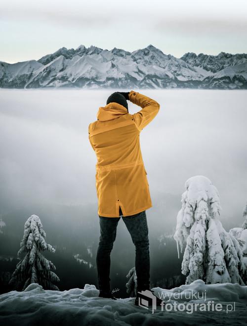 Fotografia przedstawia fotografa robiącego zdjęcie Tatrom stojąc na ścieżce wiodącej na Turbacz w Gorczańskim Parku Narodowym. Pomiędzy pasmami wisząca chmura oddziela oba plany