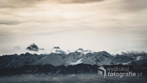 Zdjęcie wykonane z wejścia na na Turbacz w zimę. Widoczne chmury będące przecinane przez szczyty pasma górskiego