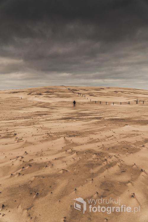 Sylwetka osoby stojącej na wydmie