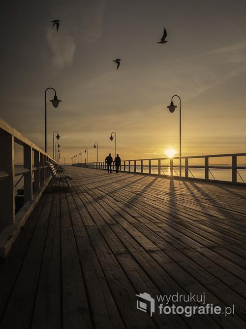 Orłowskie molo (Gdynia) w pierwszych promieniach słońca oraz pierwsi spacerowicze. Miejsce zwykle pełne ludzi, o świcie jest ostoją spokoju.