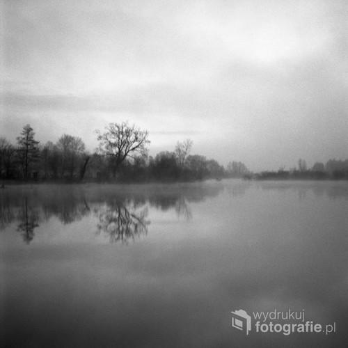 """Biebrzański Park Narodowy Kwiecień 2017  Fotografia wykonana o wschodzie słońca, analogowym, średnioformatowym aparatem na filmie czarno-białym Ilford FP4.  Jako część cyklu nagrodzona w: - MONOVISIONS PHOTOGRAPHY AWARDS 2017 (Leading Black & White Photography Magazine Award) – wyróżnienie w kategorii """"Fine Art"""".  - KONKURS NATIONAL GEOGRAPHIC POLAND """"FOTOGRAFICZNE PORANKI"""" 2017 – finalista i uczestnik warsztatów fotograficznych."""