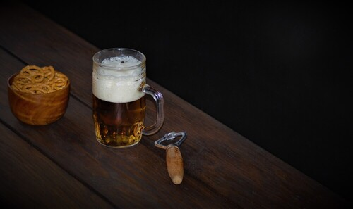 Piwo jasne z pianką podane w kuflu szklanym na przekąskę precelki w drewnianej miseczce obok kufla stary otwieracz na drewnianym stole wykonanym z desek olejonych w tle czarna ściana ,styl vintage