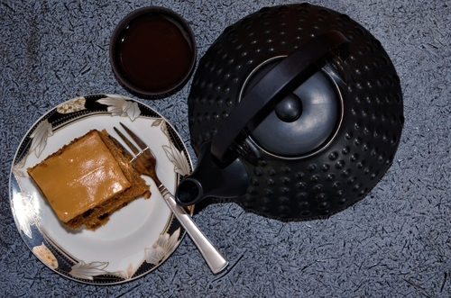 ciasto marchewkowe z budyniem karmelowym podane z czarną herbatą czajnik i filiżanka w stylu japońskim
