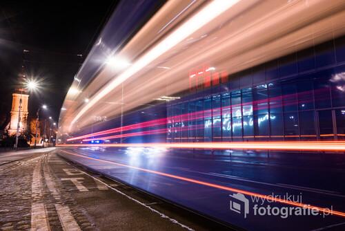 Fotografia wykonana metodą długiego naświetlania, dzięki której charakterystyczny dla Wrocławia niebieski tramwaj pozostawił jedynie kolorowe smugi, podczas przejeżdżania przez kadr. Co ciekawe, w lewej części smugi, za tramwajem uwiecznił się również radiowóz, w trakcie interwencji. Podczas naświetlania zdjęcia policjanci zatrzymali kierowcę za wykroczenie drogowe. Fotografia powstała na ulicy Traugutta. Po lewej stronie widoczny jest kościół pw św. Maurycego, natomiast w prawej części zdjęcia widać budynek ASP.