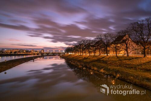 Fotografia wykonana metodą długiego naświetlania, dzięki której wieczorne chmury przyjmują lekko rozmyte kształty, co nadaje zdjęciu wrażenie ruchu. Technika ta pozwala również
