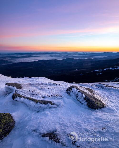 Fotografia przedstawia widok ze szczytu Szrenicy, tuż przed wschodem słońca, w zimie. W centrum kadru rozpościera się zamglona Kotlina Jeleniogórska. Wprawne oko zauważy również wieżę na ruinach zamku Chojnik.