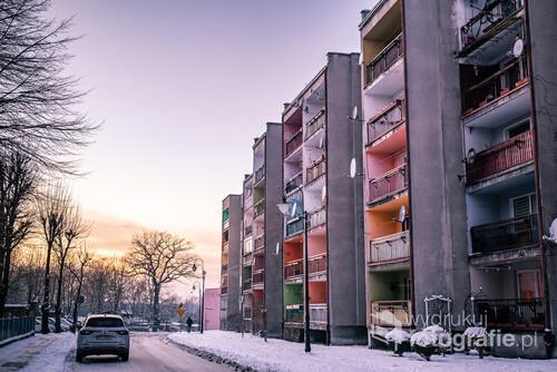 Zdjęcie powstało w niewielkim miasteczku o nazwie Pieńsk na zachodzie Polski. Szarą kolorystykę bloku mieszkalnego przełamują wielobarwnie pomalowane balkony, będące głównym tematem fotografii.