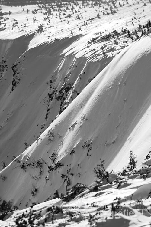 Zdjęcie wykonane spod Domu Śląskiego, pod Śnieżką. Ostre, popołudniowe światło wzmacnia kontrast między oświetloną, a zacienioną częścią zbocza, co dobrze komponuje się z czarno - białą kolorystyką fotografii.
