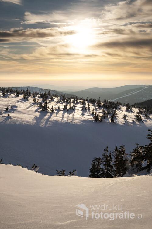 Zdjęcie powstało niedaleko Małego Szyszaka w Karkonoszach, przedstawia głównie Czeską część tego pasma górskiego. W skrajnie prawej części fotografii zauważyć można wyciąg na Medwiedin. Moim zdaniem warto zwrócić uwagę na wyraźną, poziomą linię podświetlonych, nisko zawieszonych chmur oddzielającą szczyty wzgórz na horyzoncie, od popołudniowego nieba.