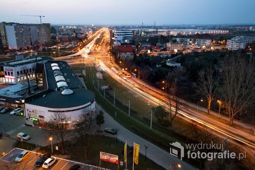 Jedna z głównych ulic wylotowych z Wrocławia, prowadząca na północ. Na horyzoncie zobaczyć można na przykład okolice Trzebnicy. Zdjęcie wykonane z dachu jednego z bloków przy ulicy Żmigrodzkiej techniką długiego naświetlania podczas tzw.