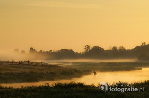 Zdjęcie zostało wykonane wczesnym rankiem we wsi Pniewo położonej na terenie Łomżyńskiego Parku Krajobrazowego Doliny Narwi i przedstawia dość typową dla tego miejsca poranną scenę wypływającego na ryby wędkarza.