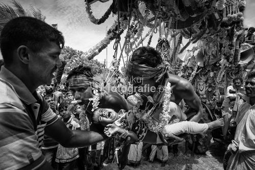 Mannar, Sri Lanka 2014. Nie zważając na ogrom traumy, którą przeżywają dzieci, raz w roku odbywa się szczególny rytuał dziękczynny. Podczas hinduistycznej procesji rodzice przekazują swoje maluchy w ręce umartwiających się mężczyzn, którzy zawieszeni na hakach huśtają się nimi przez moment. Ma być to forma podziękowania za otrzymanie potomstwa.  Fotografia zajęła I miejsce w kategorii