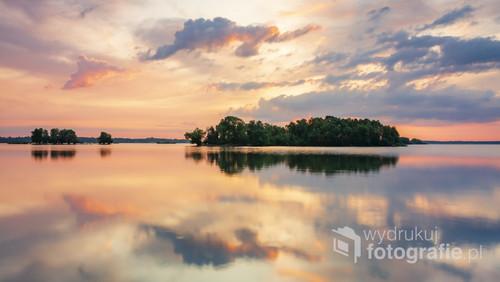 Jezioro Mietkowskie i drzewa na wodzie w czasie magicznego wschodu słońca. Zdjęcie zostało wykonane z czasem 0,8 sekundy co sprawiło że podczas bezwietrznej pogody można było zarejestrować wspaniałe odbicia wszystkiego co znajdowało się nad powierzchnią wody.