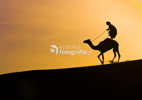 Młody dżokej ćwiczy jazdę ze swoim wielbłądem po wydmach w okolicy Maskatu, stolicy sułtanatu Omanu
