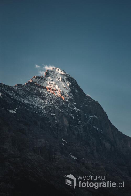 Zdjęcie przedstawia szczyt Eiger. Subtelnie oświetlany przez wyłaniające się słońce zza przeciwległej góry.