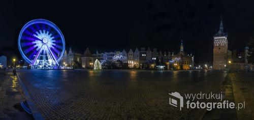 Panorama rynku w Gdańsku i pędzący na niej diabelski młyn.