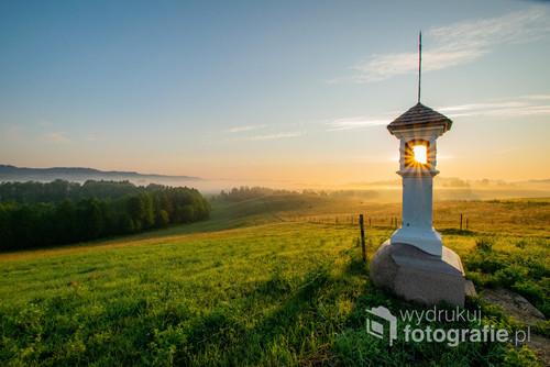 Fotografia przedstawia wschód słońca uchwycony wewnątrz przydrożnej kapliczki w miejscowości Wodziłki. Piękna i malownicza okolica położona w samym sercu Suwalskiego Parku Krajobrazowego. Zdjęcie wykonano w lipcu 2019r.