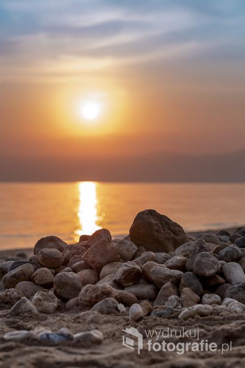 Listopadowy zachód słońca na plaży w Sweimeh, Jordania. Promienie słońca odbijają się od Morza Martwego. Na horyzoncie zarys Izraela (Zachodni Brzeg).