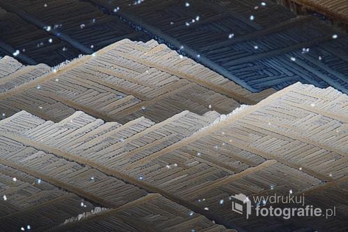 Fotografia mikroskopowa skrystalizowanego kwasku cytrynowego w świetle spolaryzowanym.
